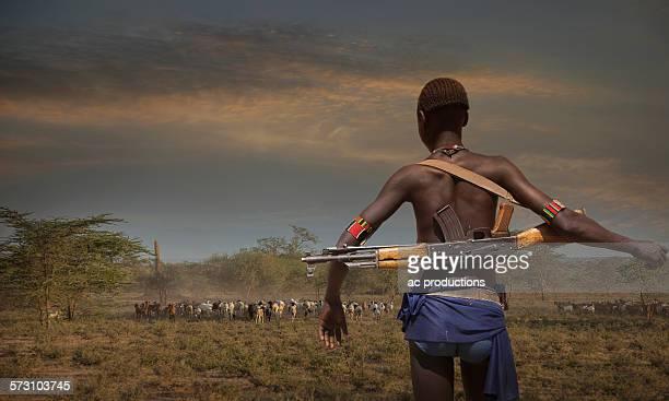 Black soldier carrying gun in open field