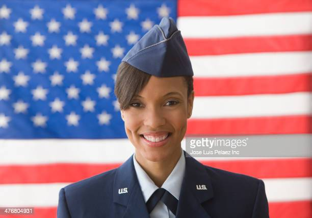 Black soldier smiling by United States flag