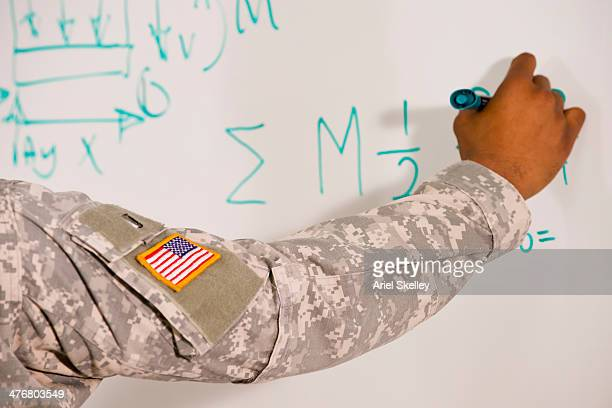 Black soldier writing on whiteboard