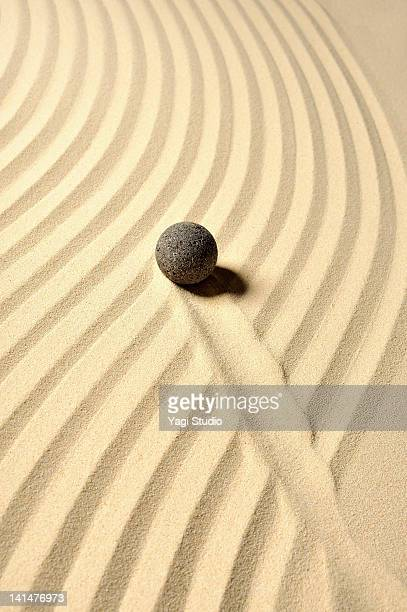 Black sphere and wave pattern in the sand pit