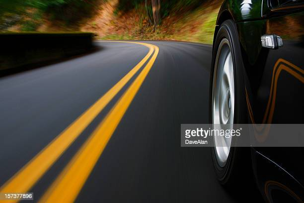 A black sports car driving around a curve