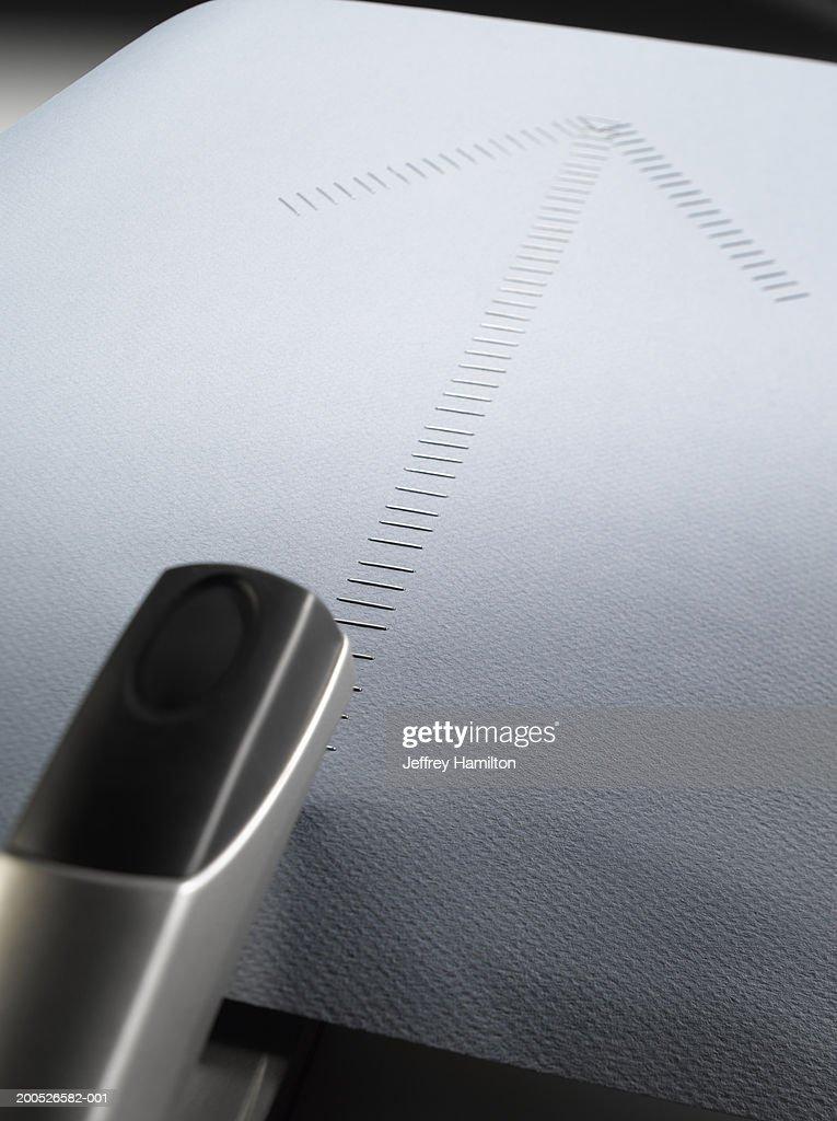 Black stapler beside large group of staples in shape of arrow