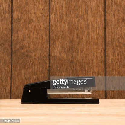 Black stapler on desk with wooden paneling.