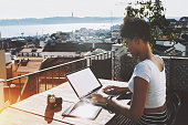 Cute Brazilian girl is sitting on balcony of old Lisbon house and sorting photos on netbook after her touristic day, charming young afro american female working on laptop with cityscape behind her