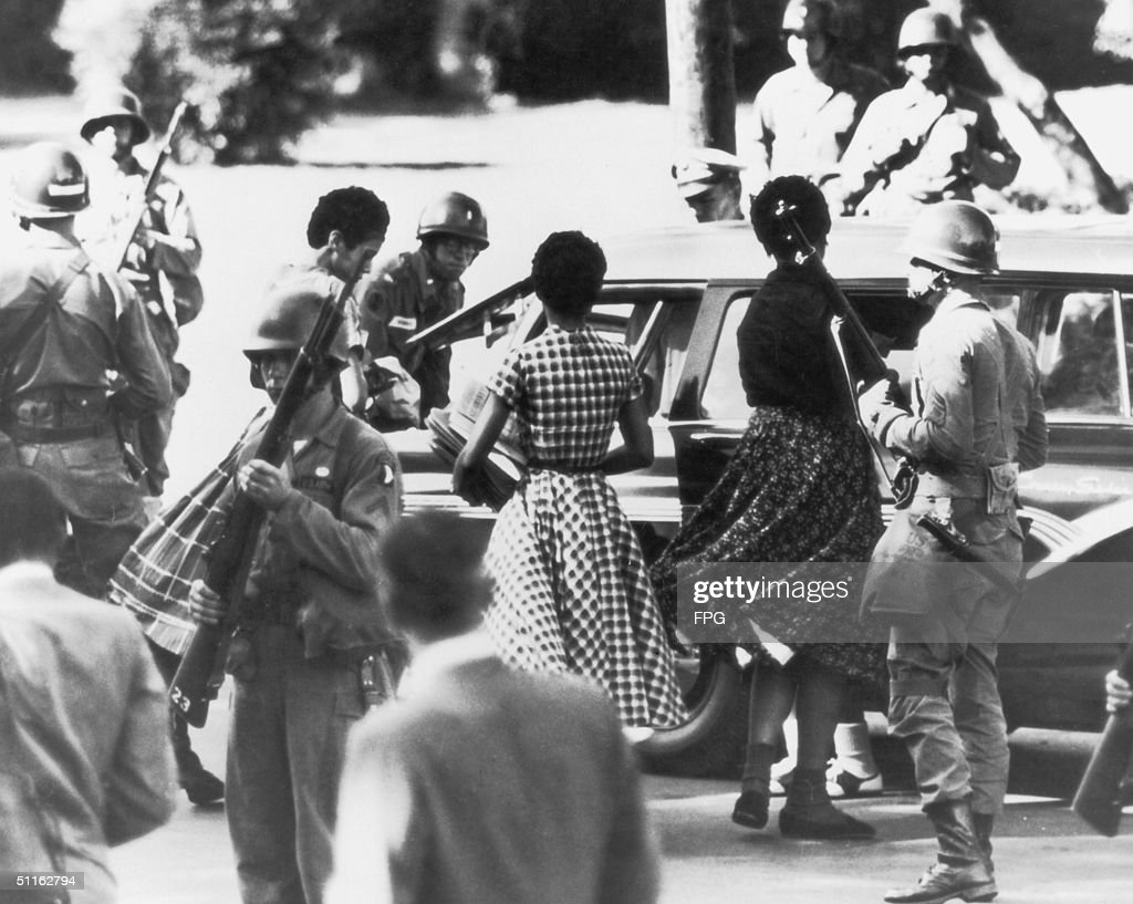 Black students are provided with a military escort when entering and leaving Little Rock Central High School, Arkansas, following the school's desegregation, 1957.
