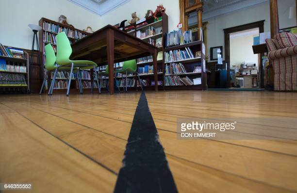 Black tape marks the US/Canada border inside the Haskell Free Library and Opera House February 28 in Stanstead Quebec and Derby Line Vermont The...