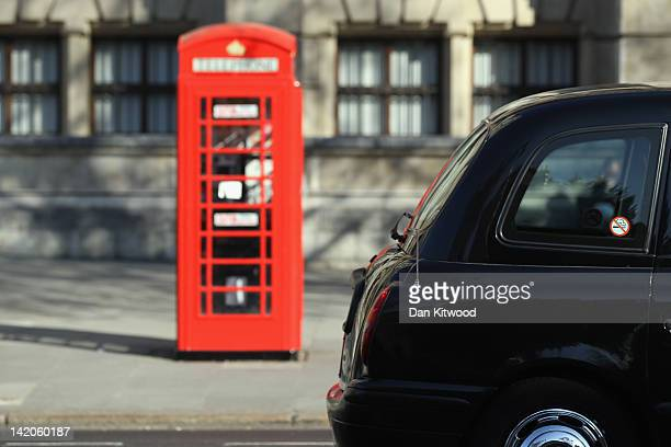 A black taxi cab drives past a telephone box on March 28 2012 in London England