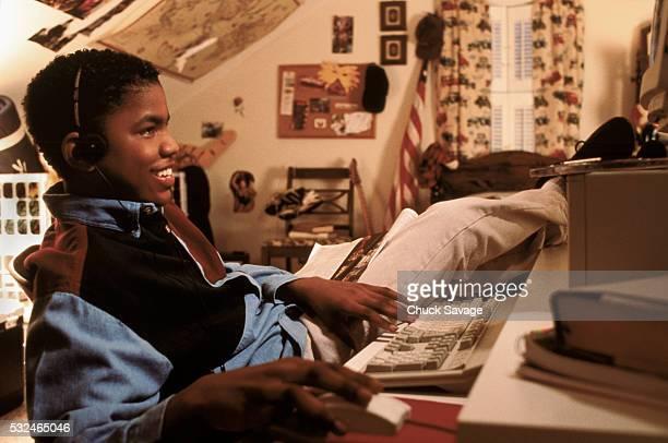 Black teen boy at computer doing homework in bedroom