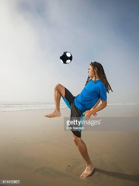 Black teenage boy playing with soccer ball on beach