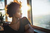 Curly charming young afro american tourist female in black dress is sitting in luxury restaurant of cruise ship near window and thoughtfully looking out the big window on ocean and warm sunset horizon