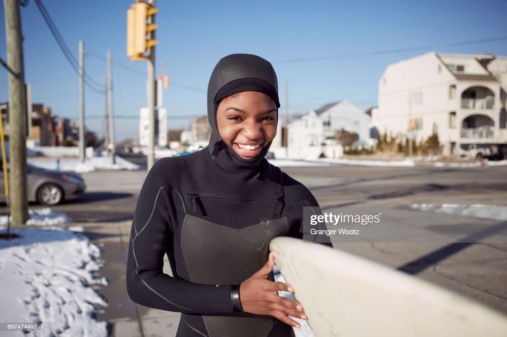 Black teenage girl in wetsuit carrying surfboard in winter