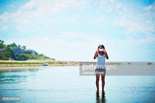 Black teenage girl taking photograph on beach