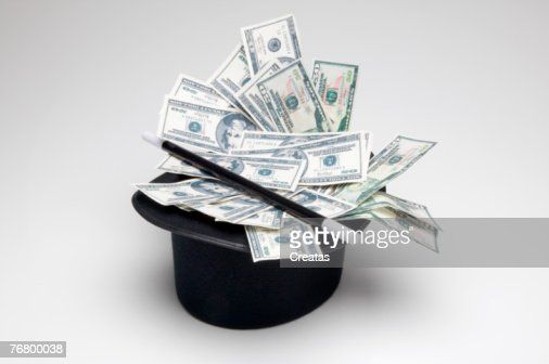 Black top hat filled with money and wand : Stock Photo