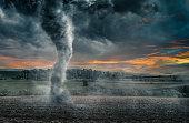 Black tornado funnel over field during thunderstorm