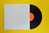 old black vinyl record with blank orange label halfway out of its white blank cover on yellow background