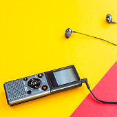 Black voice recorder with headphones on a combined yellow, blue and red background. Journalism concept. Equipment for work, interview and voice recording. Top view. Flat lay. Copyspace