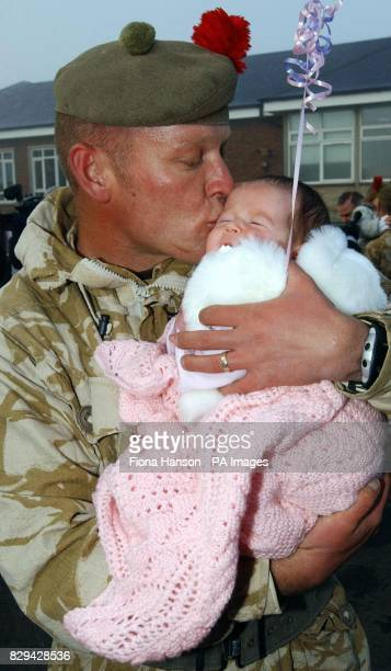 Black Watch Serjeant Allan Dunn sees newborn daughter Caitlin for the first time as he arrives at Warminster barracks after fighting outside Fallujah
