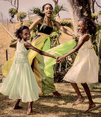 Black woman and girls dancing holding hands