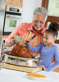 Black woman and granddaughter basting turkey
