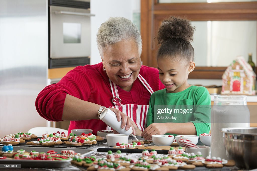 Black woman and granddaughter decorating Christmas cookies in kitchen