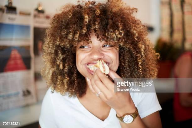 Black woman biting sandwich
