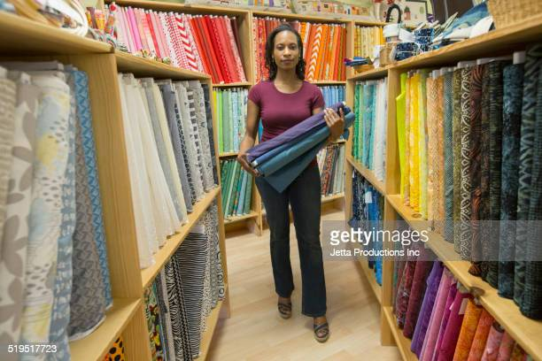 Black woman carrying fabric in store
