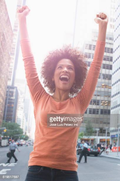 Black woman cheering on city street