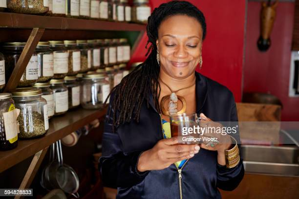 Black woman drinking tea in tea shop