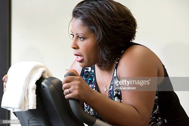 Black woman exercisng on a stationary bike in gym