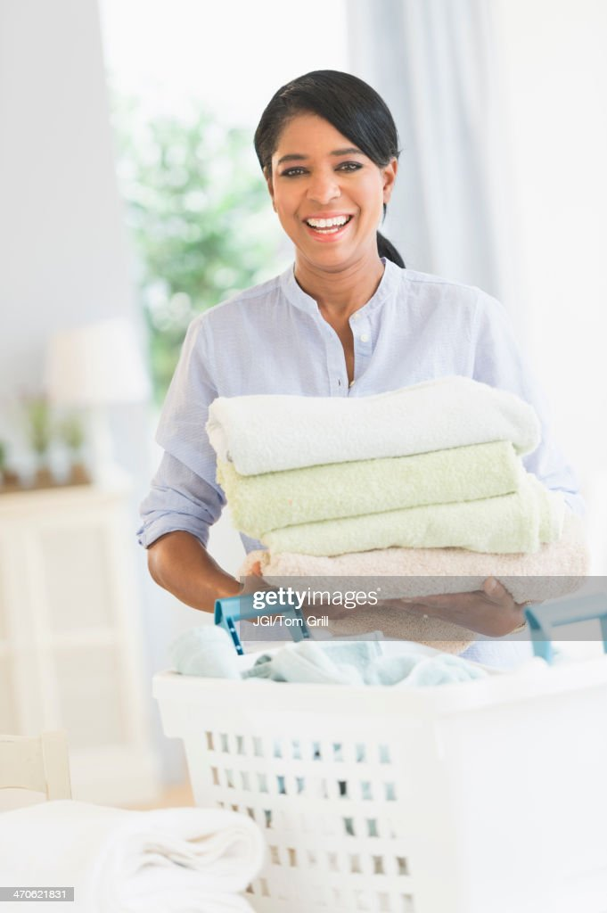 Black woman folding laundry : Stock Photo