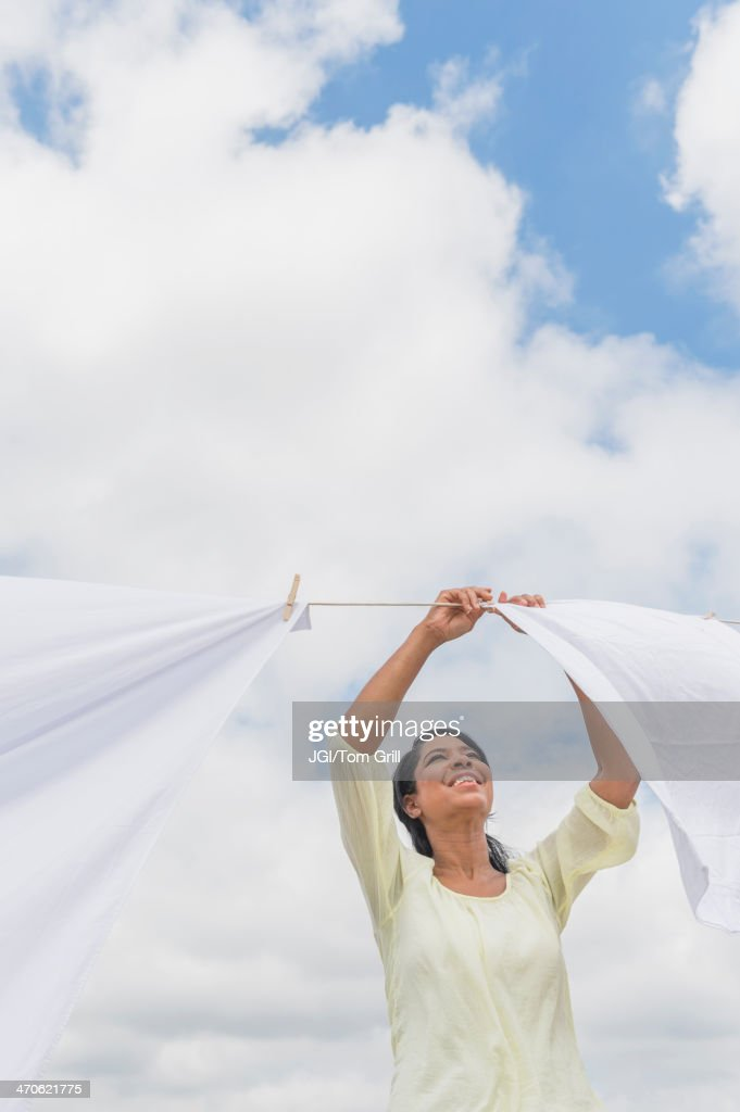 Black woman hanging sheets from clothesline : Stock Photo