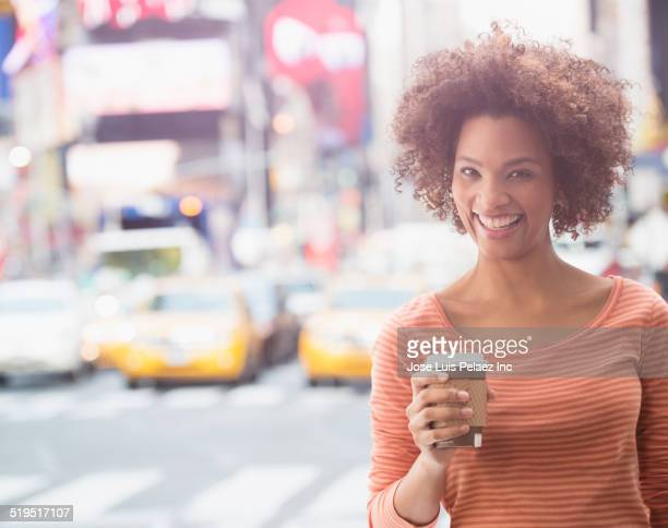 Black woman having cup of coffee in city