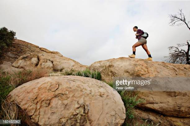 Black woman hiking on rocks