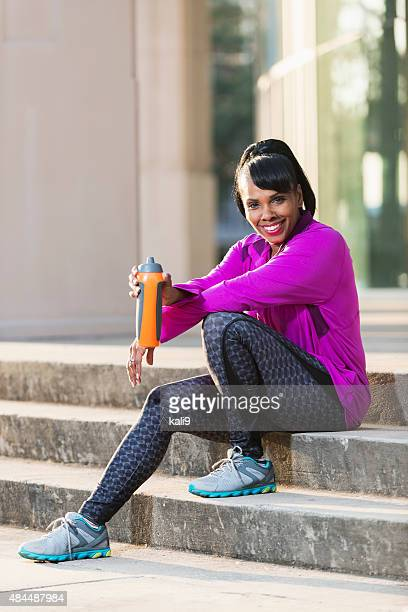 Black woman in sports clothing, taking water break