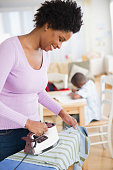Black woman ironing shirt
