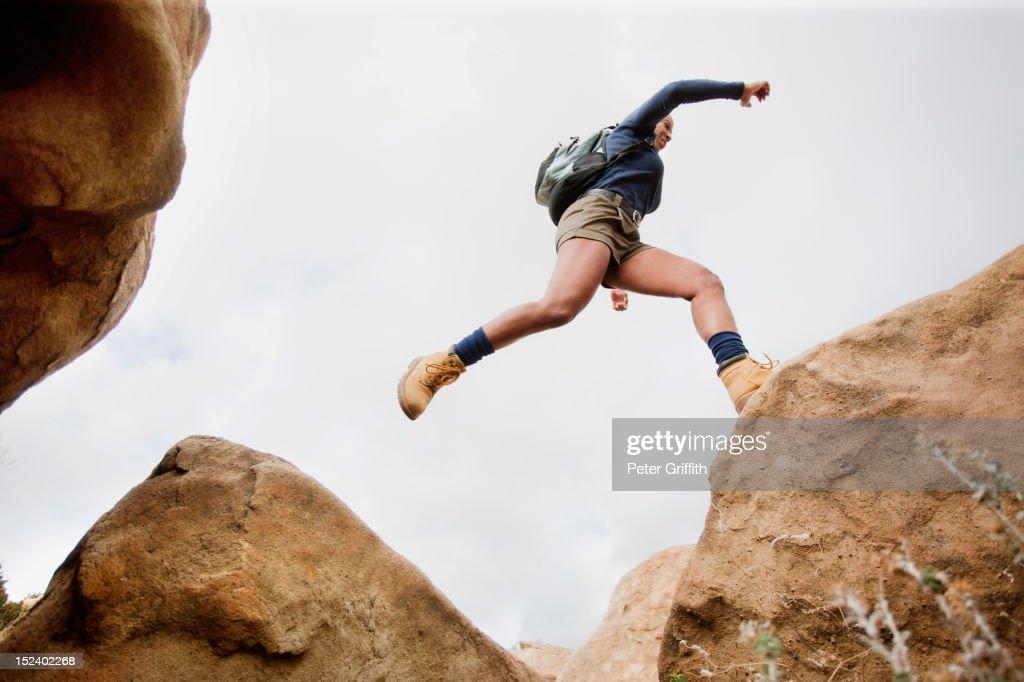 Black woman jumping across rocks