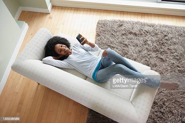 Black woman laying on sofa using cell phone