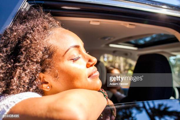 Black woman leaning out car window