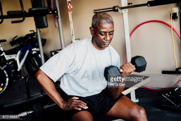 Black woman lifting weights in garage