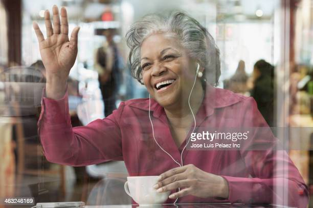 Black woman listening to headphones at cafe and waving