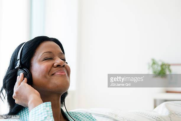 Black woman listening to headphones on sofa