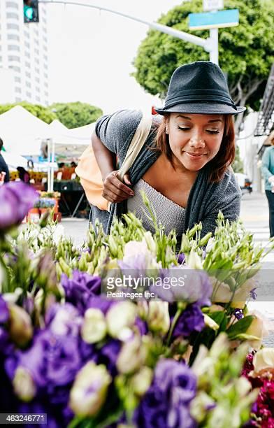 Black woman looking at flowers