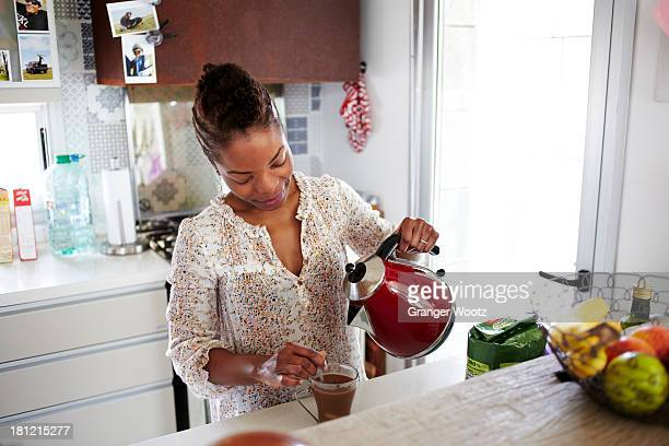 Black woman making cup of tea