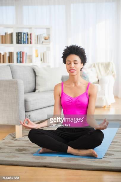 Black woman meditating on yoga mat