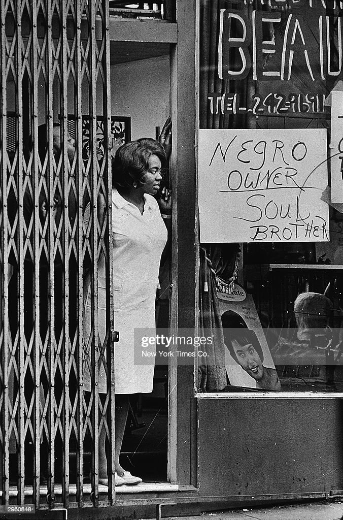 A Black woman peers from beside a gate in the door of a store with a sign in the window reading 'Negro owner' during the riots in Newark New Jersey...