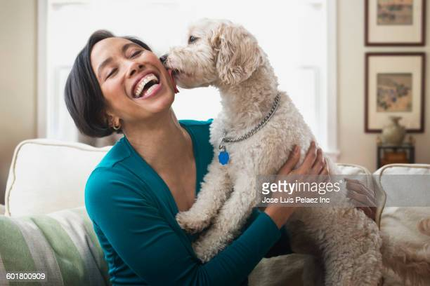 Black woman petting dog on sofa