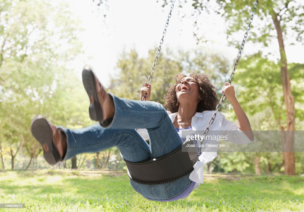 Black woman playing on swing at park