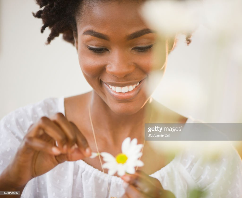 Black woman plucking petals from daisy : Stock Photo