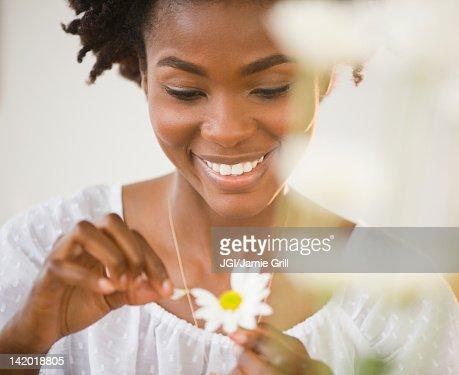 Black woman plucking petals from daisy : Stock Photo