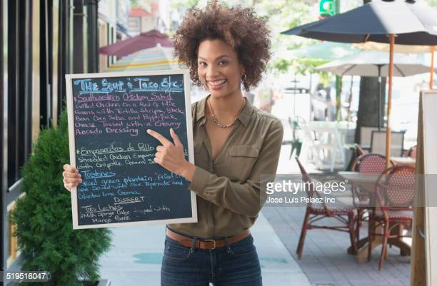 Black woman pointing to chalkboard menu outside cafe